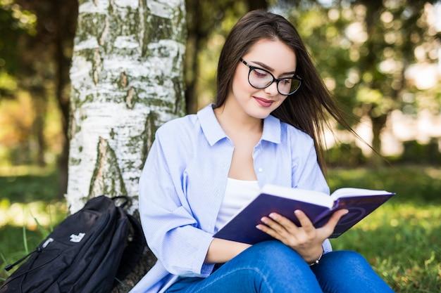 Bella ragazza seria dai capelli scuri in giacca di jeans e occhiali legge il libro contro il parco verde estivo.
