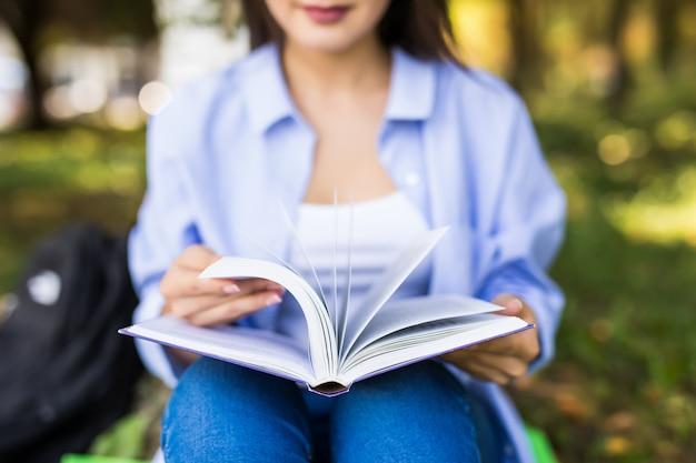 Bella ragazza seria dai capelli scuri in giacca di jeans e occhiali legge il libro nel parco.