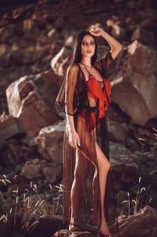 Bella ragazza sexy con grandi seni in un costume da bagno rosso a prendere il sole sulla spiaggia di sabbia nera.