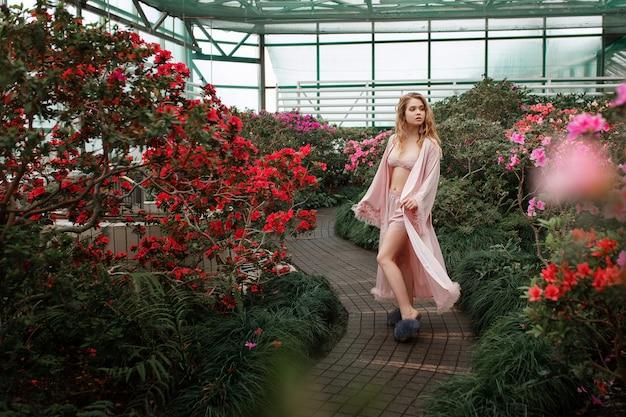 Bella ragazza sexy indossando accappatoio rosa e lingerie in piedi nel giardino fiorito.