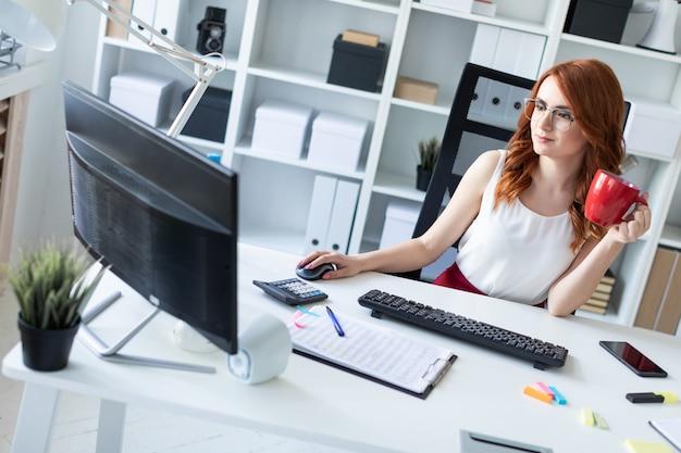 Bella ragazza si siede alla scrivania in ufficio, tiene una tazza in una mano e lavora al computer.