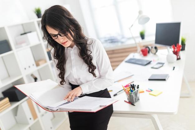 Bella ragazza si trova in ufficio, appoggiandosi sulla scrivania e scorre attraverso la cartella rossa con documenti.