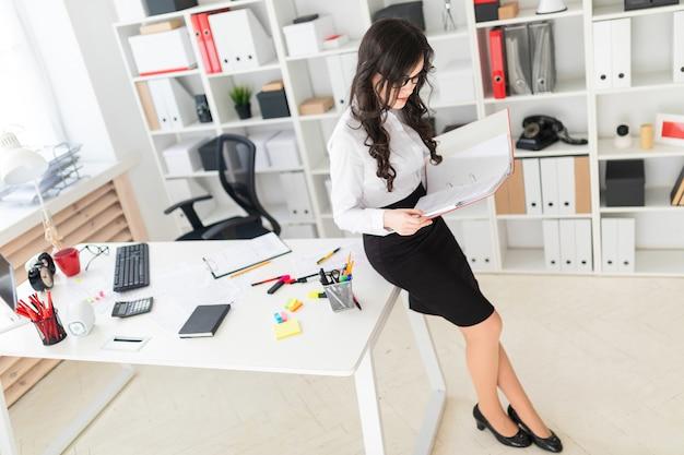 Bella ragazza si trova in ufficio, scrivania pendente e scorre attraverso la cartella rossa con documenti.