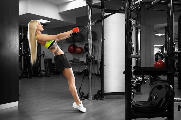 Bella ragazza snella che fa le esercitazioni in ginnastica