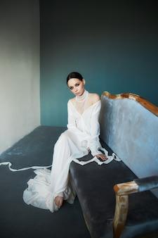 Bella ragazza snella del brunette che si siede sul sofà in un vestito bianco lungo. ritratto di una donna con gioielli sul collo. acconciatura e cosmetici perfetti della donna, nuova collezione di abiti leggeri