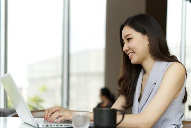 Bella ragazza sorridente asiatica astuta che lavora al computer portatile che si siede nella caffetteria.