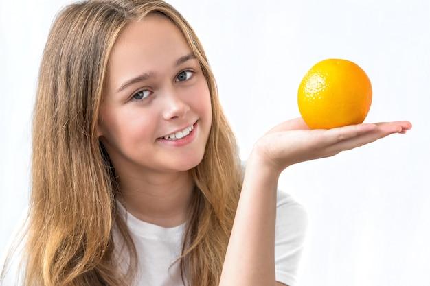 Bella ragazza sorridente con capelli lunghi in una camicia bianca che giudica arancio isolato su bianco