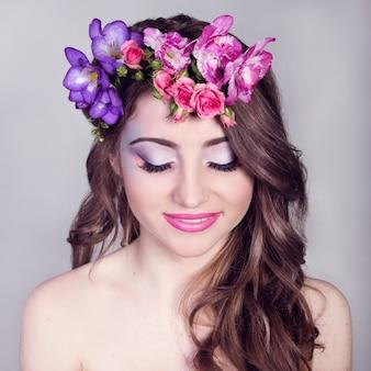 Bella ragazza sorridente con fiori tra i capelli