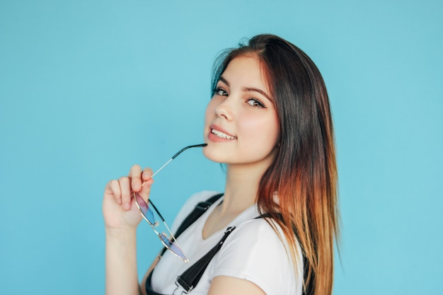 Bella ragazza sorridente con gli occhiali da sole a forma di cuore con la maglietta bianca d'uso dei capelli lunghi scuri isolata sul blu
