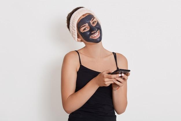 Bella ragazza sorridente con la maschera nera sul viso, tenendo lo smart phone in mano, vicino ritratto di signora facendo procedure cosmetiche isolato su muro bianco