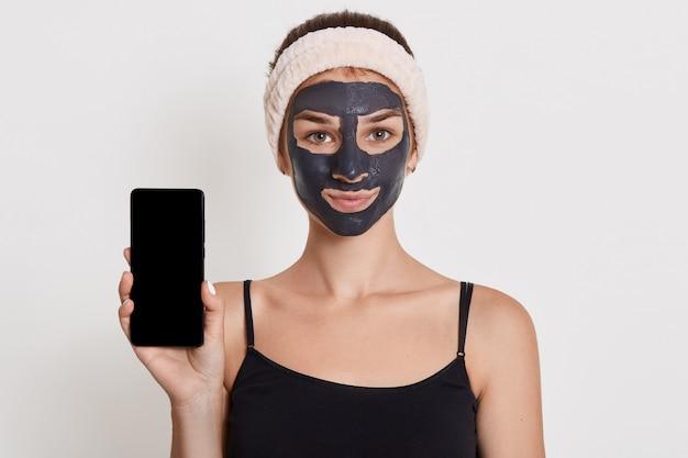 Bella ragazza sorridente con maschera nera sul viso, in possesso di smart phone con schermo vuoto, in posa isolato su bianco wall lady facendo procedure di bellezza a casa.