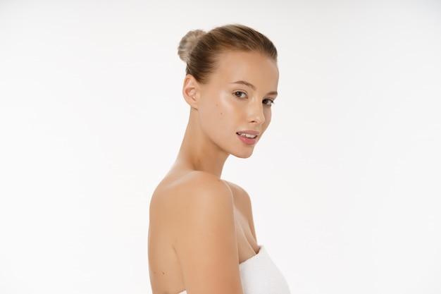 Bella ragazza sorridente con pelle pulita, trucco naturale e denti bianchi su sfondo grigio.