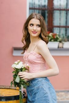 Bella ragazza sorridente con un mazzo di rose nelle sue mani