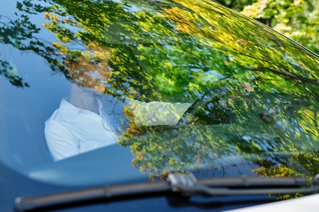 Bella ragazza sorridente del brunette al volante di un'automobile