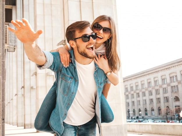 Bella ragazza sorridente e il suo ragazzo bello in abiti casual estivi. uomo che porta la sua ragazza sulla schiena e lei alzando le mani.