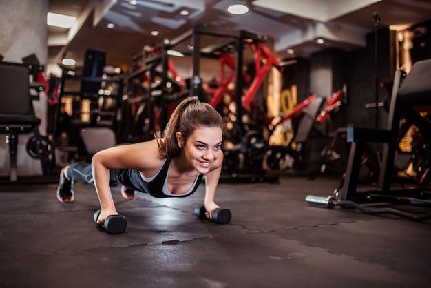 Bella ragazza sorridente facendo push-up sui pesi.