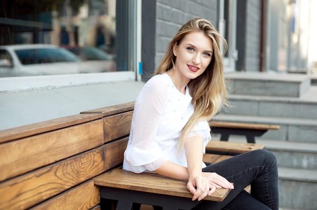 Bella ragazza sorridente felice con lunghi capelli biondi, labbra rosse, una camicia bianca in posa sulla strada in una giornata estiva.