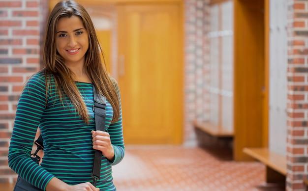 Bella ragazza sorridente nel corridoio del college
