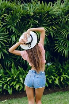 Bella ragazza sottile alla moda in piedi in un parco tropicale che torna indietro