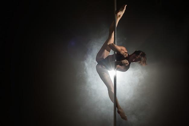 Bella ragazza sottile con pilone ballerino del palo femminile ballando