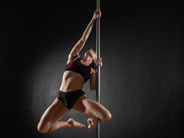 Bella ragazza sottile con pilone. ballerino femminile del palo che balla su un fondo nero