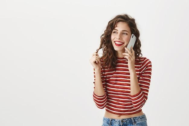Bella ragazza spensierata che parla sullo smartphone