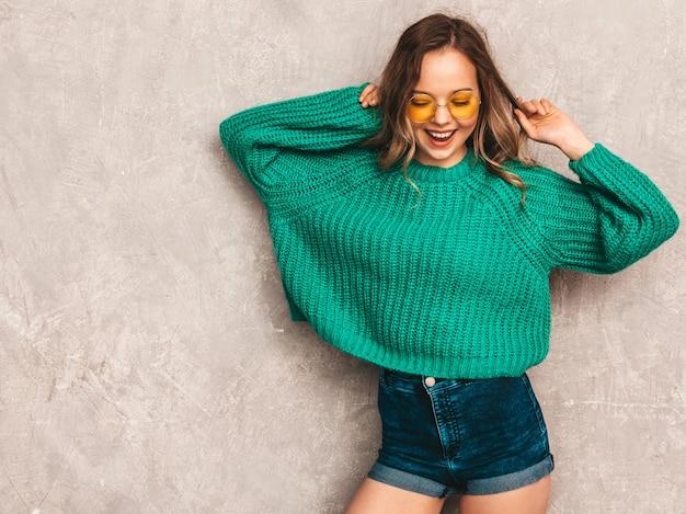Bella ragazza splendida sorridente sexy in maglione alla moda verde. donna che posa in occhiali da sole rotondi. la modella si diverte