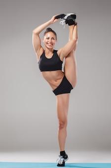 Bella ragazza sportiva che sta nella posa dell'acrobata o nel asana di yoga