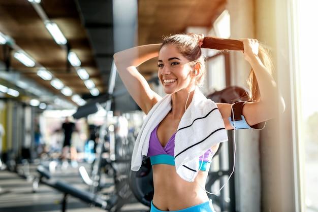 Bella ragazza sportiva sexy che lega i suoi capelli prima del duro allenamento in una palestra. sorridendo e ascoltando la musica con le cuffie in testa.