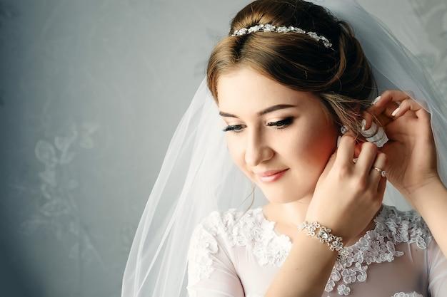 Bella ragazza, sposa in abito bianco sullo sfondo dell'appartamento. matrimonio, raduno della sposa, creazione della famiglia.