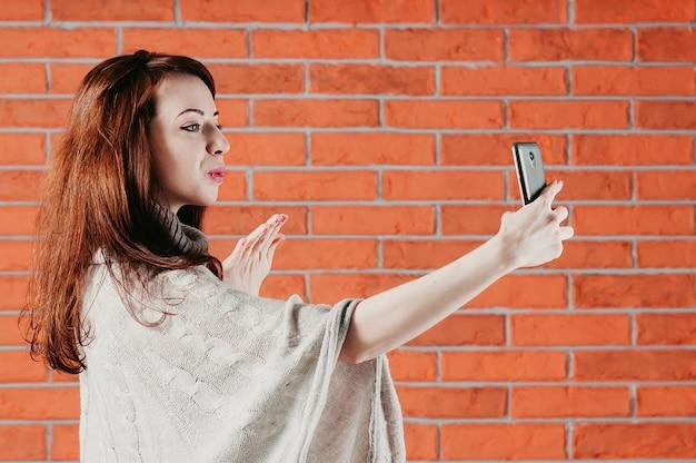 Bella ragazza sta facendo selfie con lo smartphone, inviando bacio dell'aria, vista mezza faccia