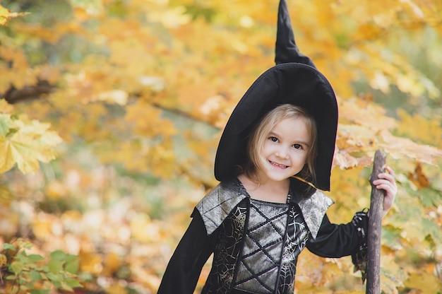Bella ragazza strega. bambina in cui i costumi celebrano halloween all'aperto e si divertono. i bambini scherzano o trattano