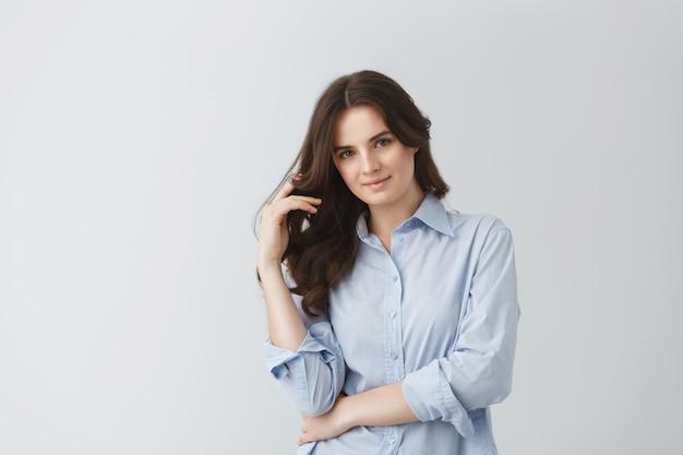 Bella ragazza studentessa in camicia blu che tiene la mano in lunghi capelli ondulati in posa per l'articolo di giornale studentesco sui migliori studenti dell'anno.