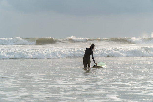 Bella ragazza su una tavola da surf nell'oceano
