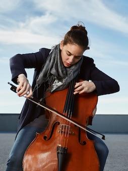 Bella ragazza suona il violoncello con passione in un ambiente concreto