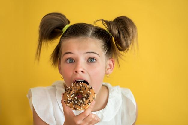 Bella ragazza teenager che mangia una ciambella.
