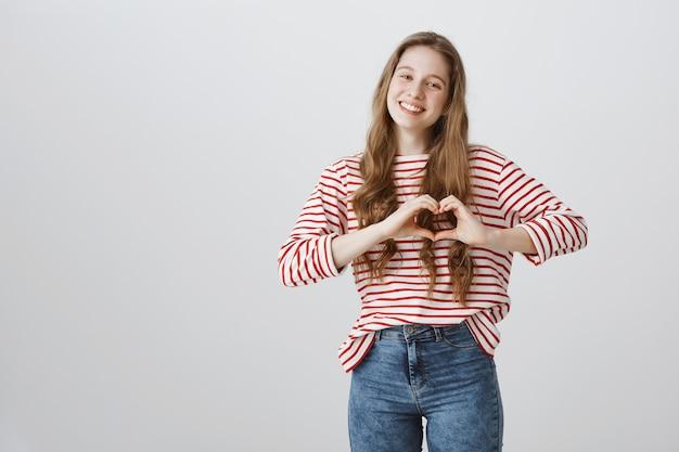 Bella ragazza tenera che mostra il gesto del cuore, mostrando amore e cura
