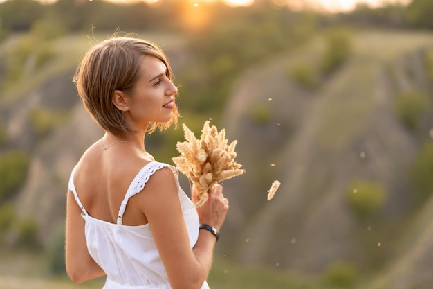 Bella ragazza tenera in un prendisole bianco cammina al tramonto in un campo con un bouquet di spighette.