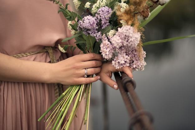 Bella ragazza tenera in un vestito color pesca che cammina su un ponte di legno rurale con un mazzo di fiori in mano