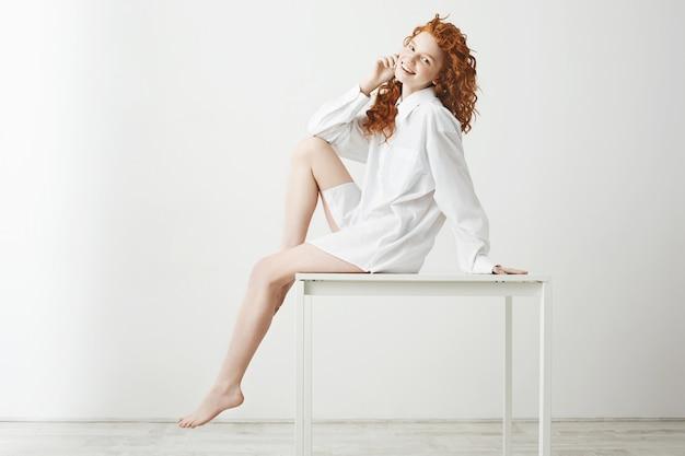 Bella ragazza tenera sveglia con la posa di risata dei capelli rossi ricci che si siede sulla tavola sopra fondo bianco. copia spazio.