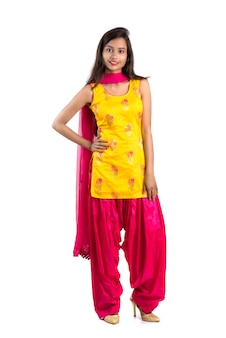 Bella ragazza tradizionale indiana che posa sul fondo bianco.