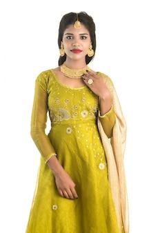 Bella ragazza tradizionale indiana che posa sulla parete bianca