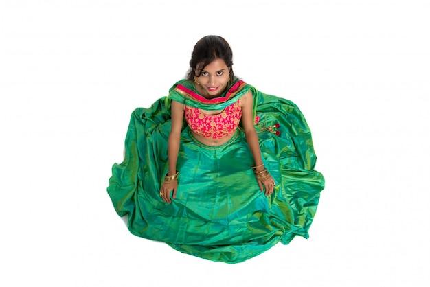 Bella ragazza tradizionale indiana che si siede e che posa sul fondo bianco.