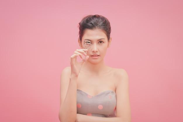 Bella ragazza trucco con cosmetici. le belle donne usano cosmetici adatti al viso.