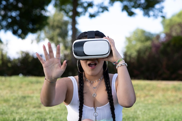 Bella ragazza utilizzando occhiali per realtà virtuale in un parco