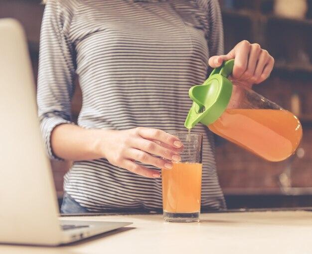 Bella ragazza versando il succo nel bicchiere.