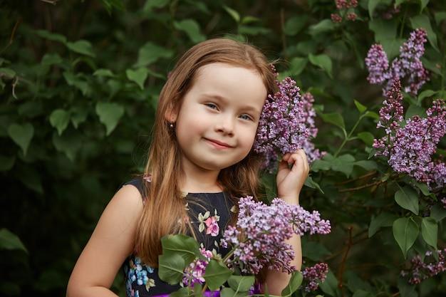 Bella ragazza vestito in posa vicino a un cespuglio di lillà