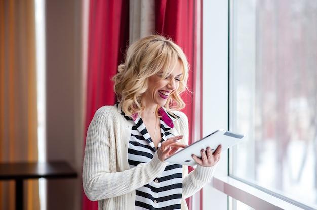 Bella ragazza vicino alla finestra, bionda, laptop