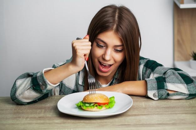 Bella ragazza vuole mangiare hamburger dannoso