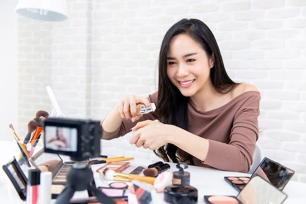 Bella recensione asiatica di bellezza della donna che registra registrazione cosmetica
